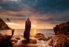 Обои с девушкой стоящей на камнях у моря рядом с дракон…