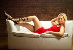 Красивая девушка блондинка на диване в красном платье