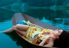Красивая девушка брюнетка в лодке на озере