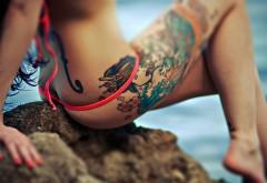 Татуировка на теле девушки на фоне моря