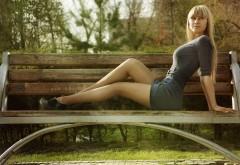 Красивая девушка, расслабляющаяся на скамейке